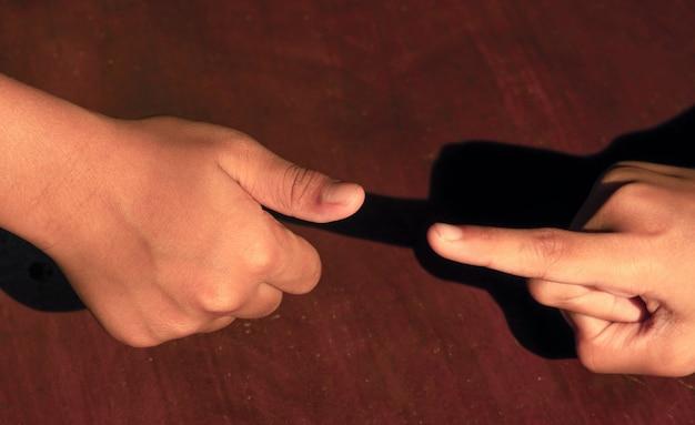 Игровые каменные ножницы для бумаги на деревянном столе с помощью пальца и большого пальца. концепция бизнес-конкуренции.