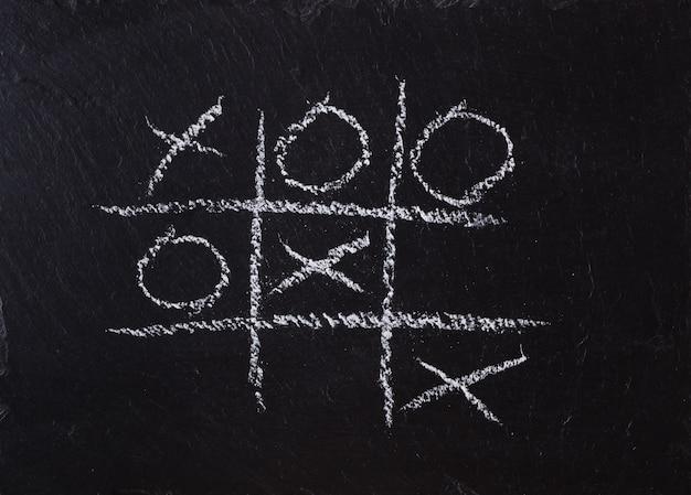Game tic tac toe on black slate board