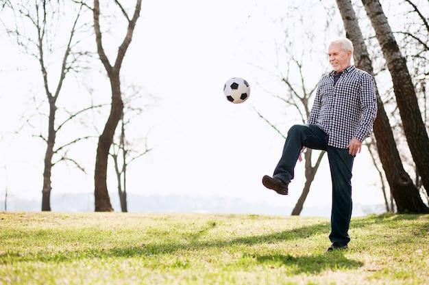 Игра с мячом. восторженный зрелый мужчина тренируется с мячом и поднимающейся ногой