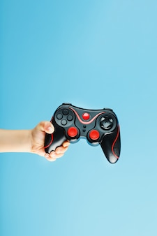 Gamepad on a blue surface holds by child's hand