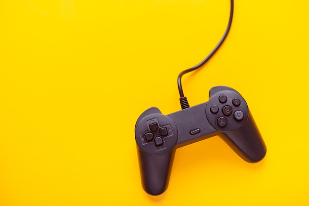 黄色の背景のゲームコンソールからのゲームパッド接続ワイヤー