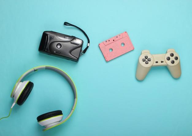 Gamepad, stereo headphones, audio cassette, film camera on a blue surface