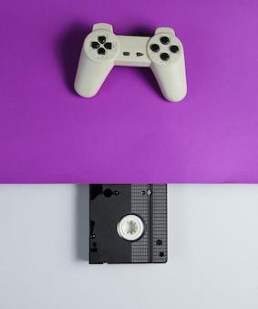 ゲームパッド、紫灰色のテーブルの上のビデオカセット。 80年代のレトロなスタイル。上面図