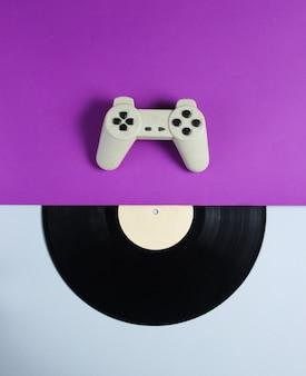 ゲームパッド、紫灰色のテーブルにビニールレコード。レトロなスタイル。上面図