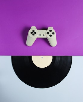 Gamepad, vinyl record on a purple gray table. retro style. top view