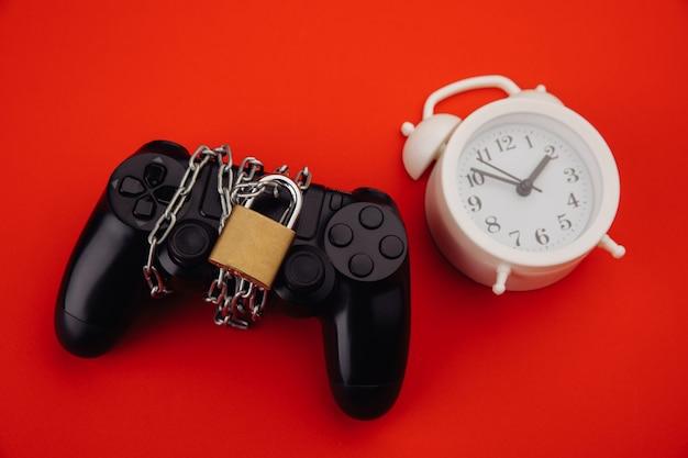 南京錠と白い目覚まし時計付きのゲームパッド