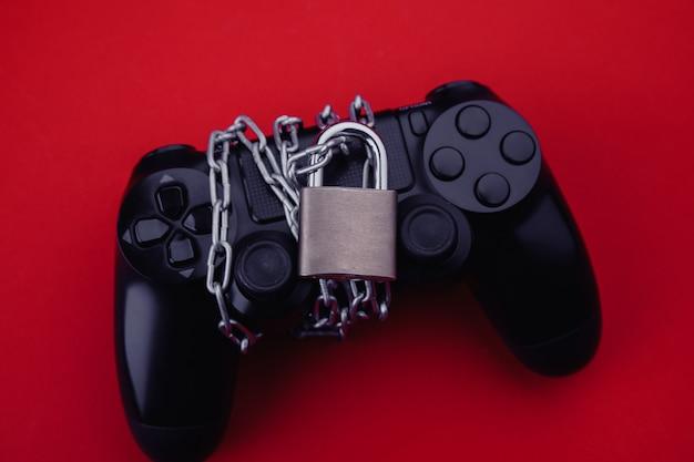 南京錠付きのゲームパッド、ゲーム中毒のコンセプト。