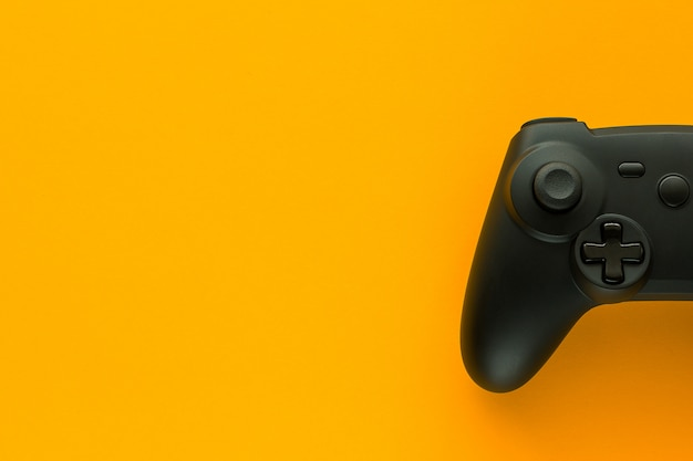 A gamepad on a yellow table and copy space