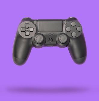 紫色の紙の背景にゲームパッド