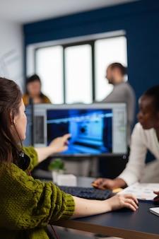 Создатель геймера объясняет африканскому рабочему, как тестирует интерфейс игрового уровня, разрабатывает новый дизайн в творческом офисе, указывая на экран