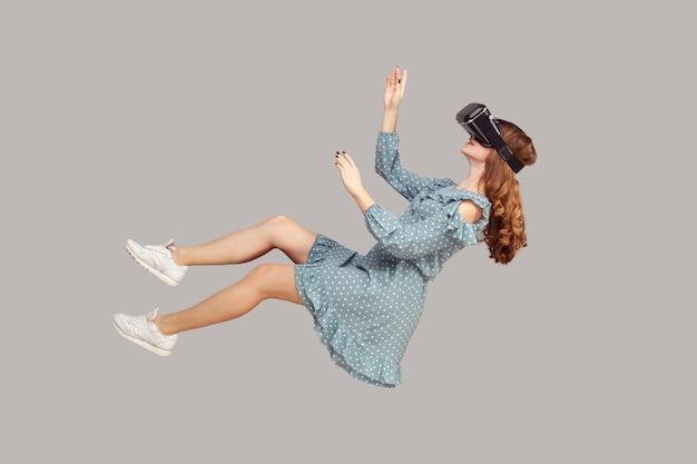 Девушка-геймер в платье парит в воздухе, левитирует в очках виртуальной реальности на голове, играет в vr