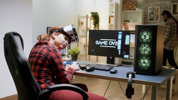 Девушка-геймер проигрывает турнир по видеоиграм, играя с гарнитурой vr поздно ночью в своей комнате