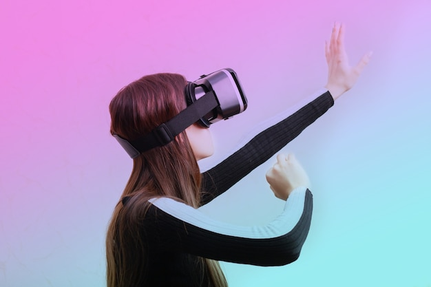 Gamer girl playing video game in glasses helmet virtual reality