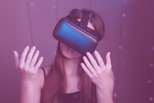 Геймер девушка играет в видеоигры в очках, шлем виртуальной реальности