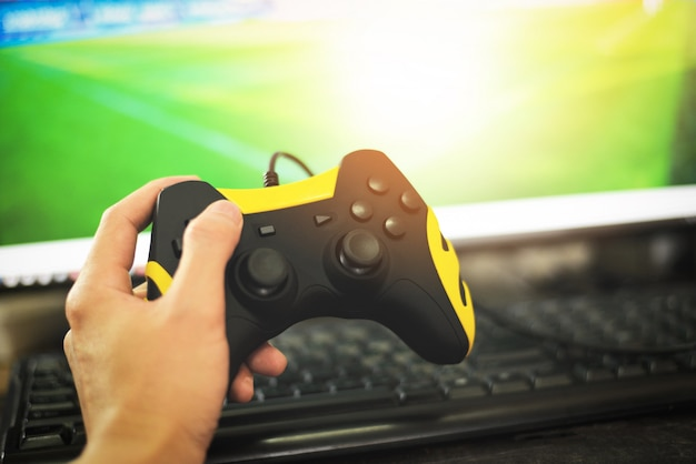 Gamer and guy controller with game pad joystick on hand playing gaming and watching video on tv or computer games console - the boy holding hobby playful enjoyment fun and entertainment