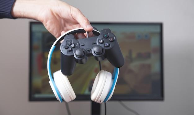 Gamer holding joystick and headphones