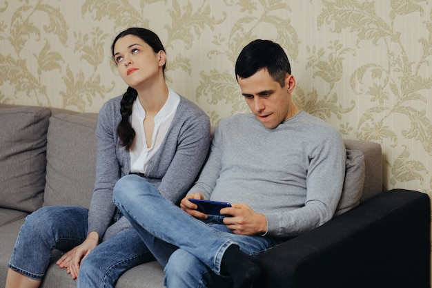 Gamer husband plays on smartphone, angry wife sits nearby