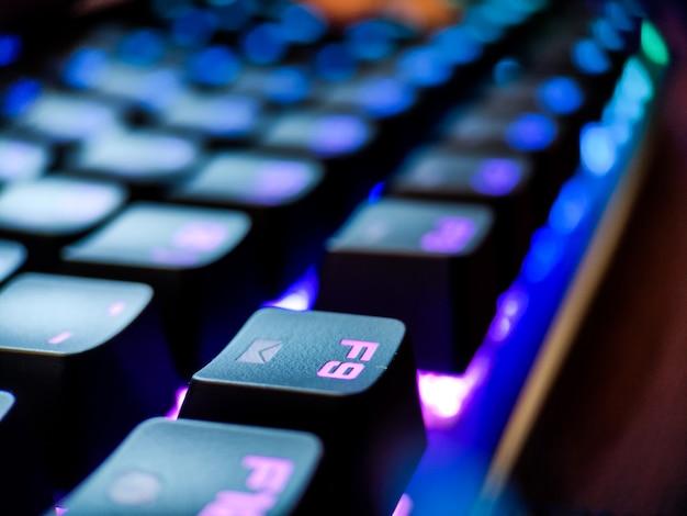 네온 백라이트 매크로 디포커스가 있는 게이머 키보드가 닫힙니다. 온라인 게임 및 가상 현실 개념 배경. 고품질 사진