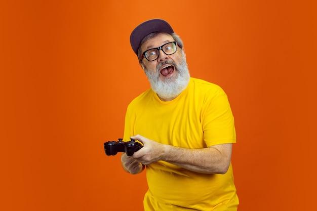 ゲーマーマン。オレンジ色のスタジオの背景に分離されたデバイス、ガジェットを使用して流行に敏感なシニア男性の肖像画。技術と楽しい高齢者のライフスタイルのコンセプト。トレンディな色、永遠に若さ。広告のコピースペース。