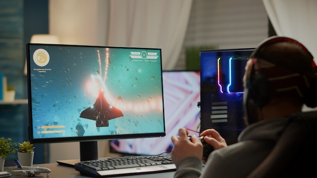 Gamer player with headphones and joypad performing space shooter video game during gaming championship. online streaming cyber performing at virtual esports tournament using wireless joystick