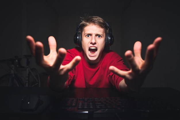 Gamer playing games at night on a computer and emotional looking at the camera