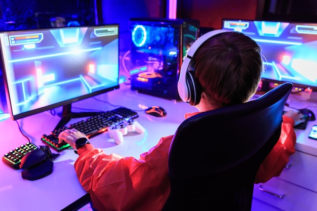 Gamer playing online game on pc in dark room.