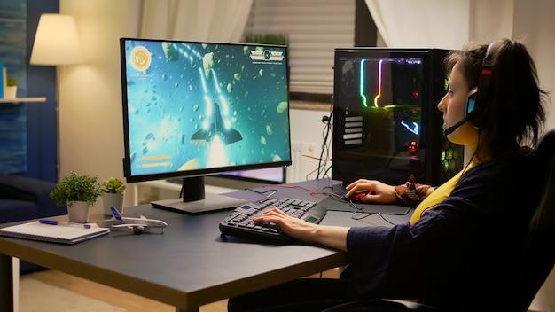 Giocatore che gioca a videogiochi sparatutto spaziali online utilizzando un computer potente e una tastiera rgb