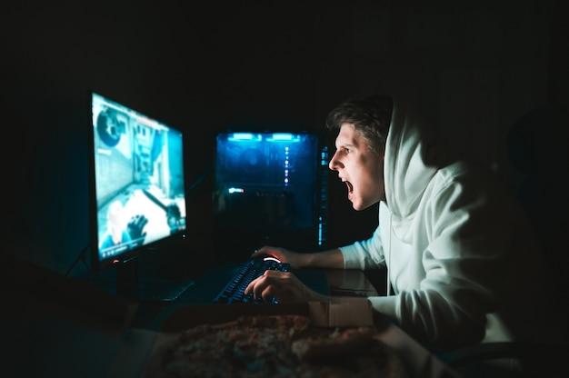 Геймер сидит дома за столом у компьютера и ест пиццу