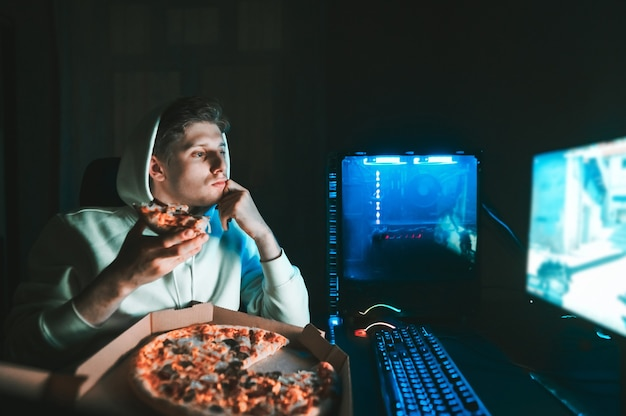 Gamer sits at home at the table at the computer and eats pizza