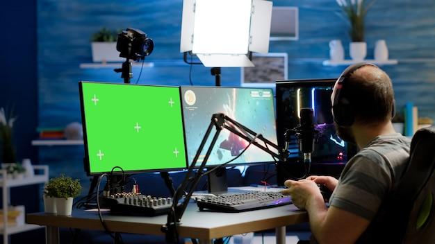 녹색 화면, 조롱, 크로마 키 디스플레이가 있는 강력한 전문 컴퓨터에서 온라인 비디오 게임을 스트리밍하는 게이머. 무선 컨트롤러를 들고 격리된 데스크탑에서 공간 사수 게임을 하는 스트리머