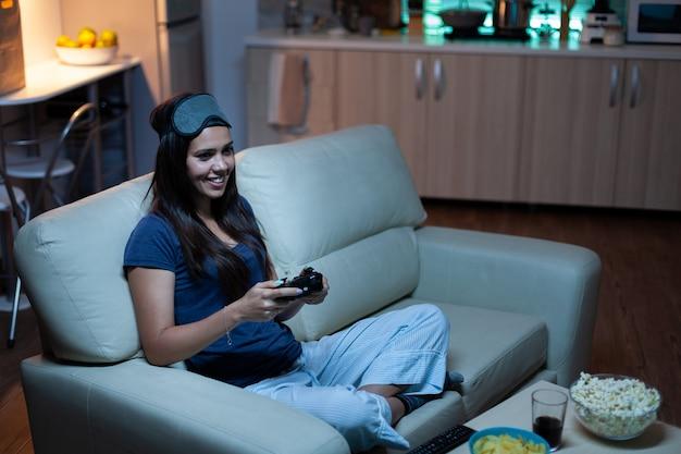 거실 소파에 앉아 콘솔에서 조이스틱을 사용하여 비디오 게임을 하는 게이머. 컨트롤러 게임패드 키패드 플레이 스테이션 게임을 사용하고 전자 게임에서 승리하는 것을 즐기는 흥분된 결정된 여성