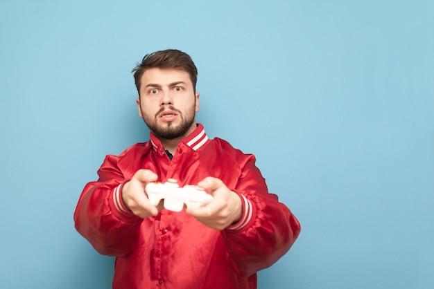 赤いジャケットにひげを持つゲーマーは、彼の手にジョイスティックを持つ青の上に立つ
