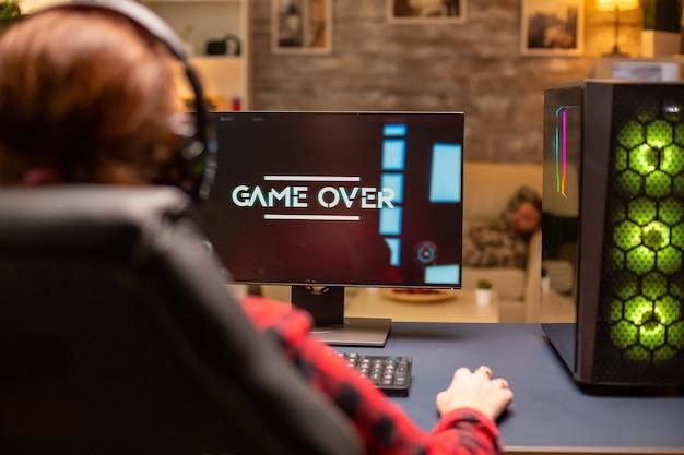 居間で夜遅く遊んでいるビデオゲームで負けるゲーマー女性。
