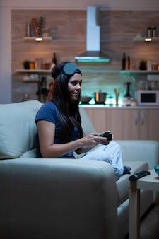 Женщина-геймер играет в видеоигры на консоли с помощью контроллера и джойстиков, сидя на диване перед телевизором