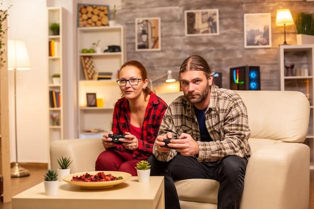 ゲーマーは、ワイヤレスコントローラーを手にテレビでビデオゲームをプレイするカップルです。