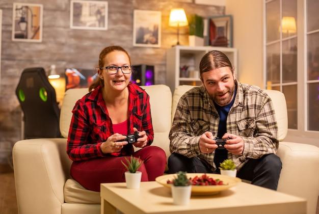 무선 컨트롤러를 손에 들고 tv에서 비디오 게임을 하는 게이머 커플.