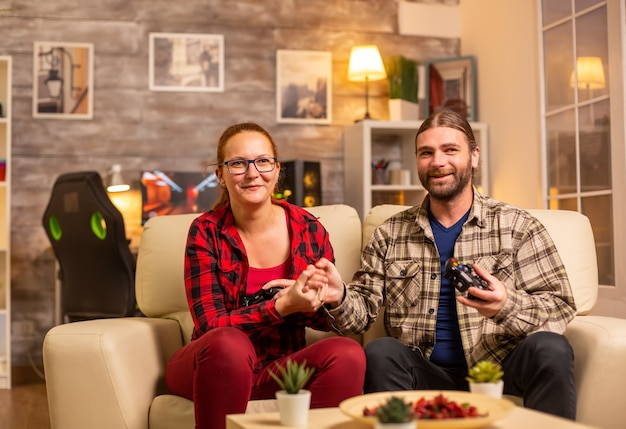Gamers couple playing video games on the tv with wireless controllers in hands.