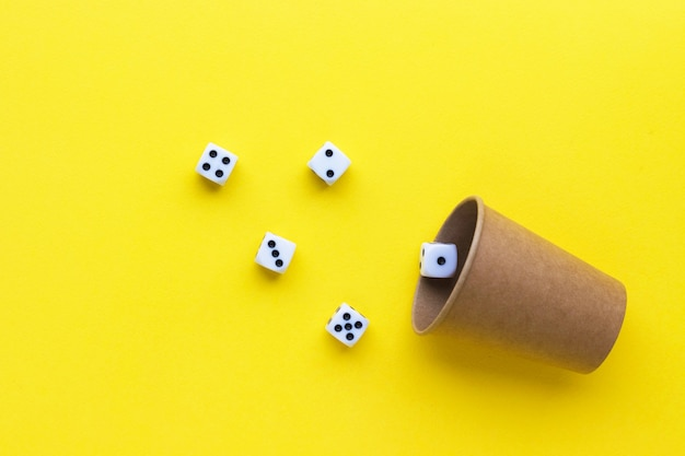 Gaming dice and cardboard cup on yellow background. playing cube with numbers. items for board games. flat lay, top view with copy space.