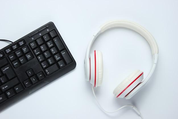 ゲーム機器。白い背景の上のキーボードとヘッドフォン。音楽のコンセプト。コンピュータゲームの競争。上面図