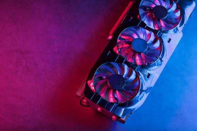 Игровая видеокарта с неоновой пурпурно-голубой подсветкой и высокоскоростными вентиляторами. видеочип для майнинга и мощных игр в концепции киберпанка.