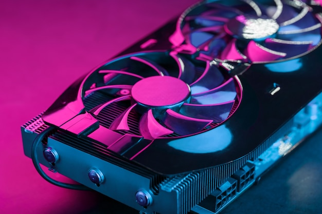 Игровая видеокарта с неоновой пурпурной подсветкой и скоростными вентиляторами. видеочип для майнинга и мощных игр в концепции киберпанка. выборочный фокус