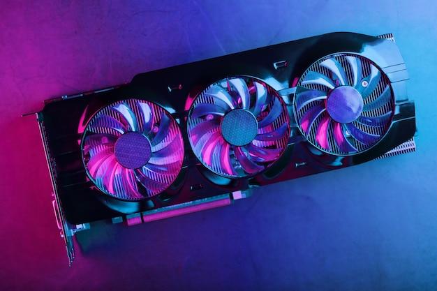 Игровая видеокарта с неоновой пурпурной подсветкой и скоростными вентиляторами. видеочип для майнинга и мощных игр в концепции киберпанка.