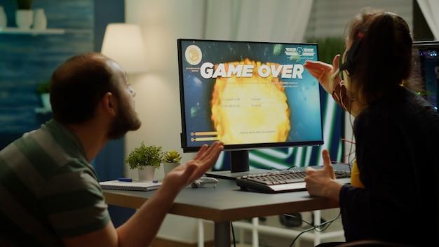 神経質なプロカップルゲーマーのためにゲームをし、プロのヘッドセットを使用して仮想競技トーナメント中にスペースシューティングゲームをプレイします。 rgbの強力なコンピューターを使用して実行する悲しいオンラインストリーミングサイバー。