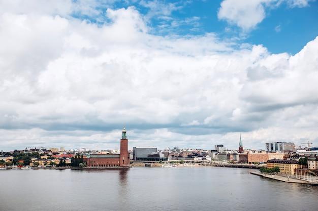 Сценарная панорама лета архитектуры старого городка (gamla stan) в стокгольме, швеции. вид с холма монтелиусваген на остров риддархольм и башни церкви. озеро маларен с голубое небо, белые облака.