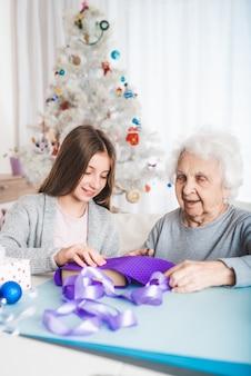 クリスマスに豪華な紙でおばあちゃんが贈り物を飾るのを手伝う孫娘