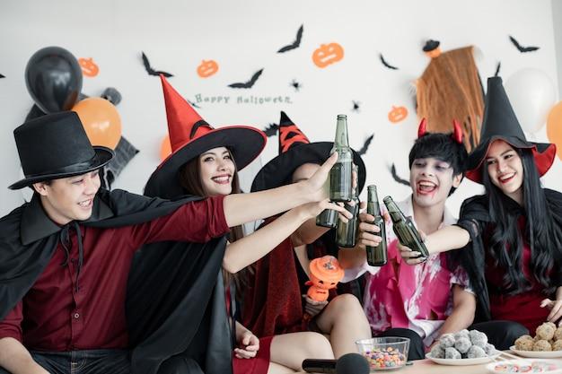 Банда молодой азиатки в костюме ведьмы, волшебника празднует вечеринку в честь хэллоуина за звоном бутылки и напитком в комнате. группа подростков тайский с празднованием хэллоуина. концепция вечеринки хэллоуин дома.