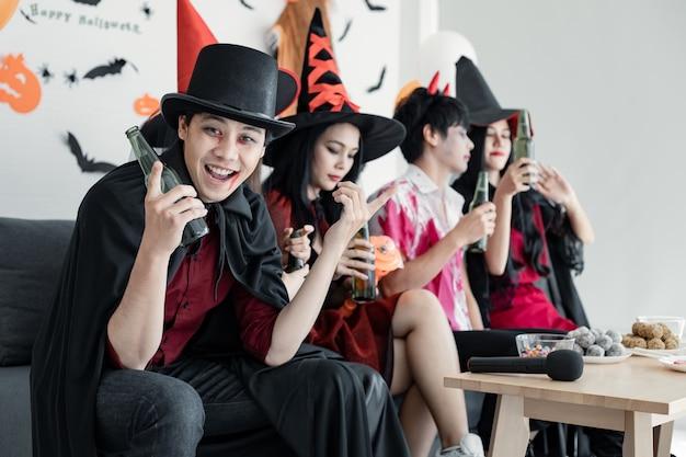 Банда молодой азиатки в костюме ведьмы, волшебника с праздником хэллоуина танцует, выпивает и пьет в комнате. группа подростков тайский с празднованием хэллоуина. концепция вечеринки хэллоуин дома.