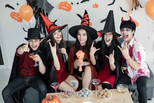 Банда молодой азиатки в костюме ведьмы, волшебника с праздником хэллоуина, чтобы спеть песню и выпить, десерт в комнате. группа подростков тайский с празднованием хэллоуина. концепция вечеринки хэллоуин дома.