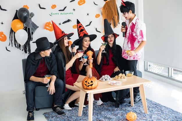 의상 마녀를 입은 젊은 아시아인, 노래와 음료를 위한 할로윈 파티를 축하하는 마법사, 방에서 디저트. 할로윈을 축하하는 그룹 십대 태국어. 집에서 개념 파티 할로윈입니다.