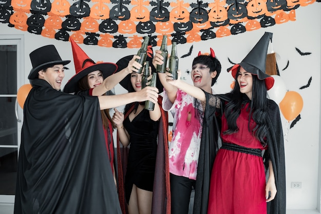 Gang of young asian in costume witch, wizard with celebrate halloween party for dance and drink and drunk in the room. group teen thai with celebrate halloween. concept party halloween at home.